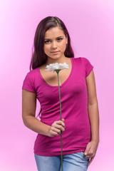 girl holding flower on pink background.