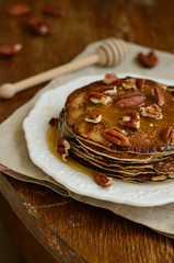 Homemade thin pancakes with honey and pecan nuts on white porcel