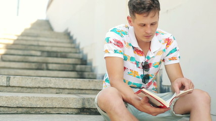 Young trendy man reading book on stairs in the city