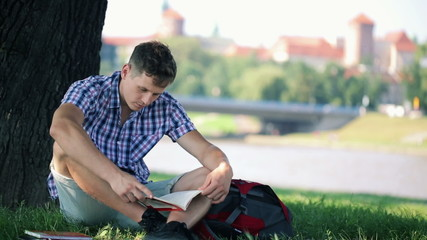 Young student reading book in city park