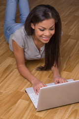 Smiling young woman lying on wood flooring.