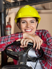 Female Engineer Leaning On Forklift's Steering Wheel