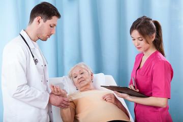 Doctors diagnosing elderly woman