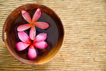 Two Pink frangipani in water wooden bowl on Brown straw mat