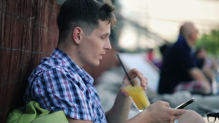 Trendy man texting on smartphone drinking juice in outdoor cafe