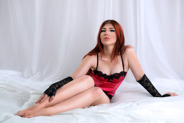 Seductive redhead woman in sexy lingerie sitting in bed