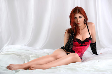 Seductive woman wearing pink lingerie sitting in bed