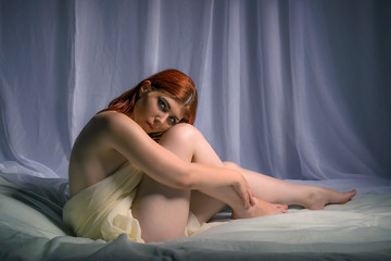 Young woman sitting in bed covered in sheets