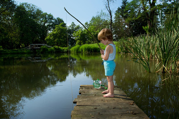 Little Boy Fishing from Wooden Dock on a Lake in Sunny Day