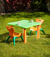 toy plastic chair and table on grass at yard