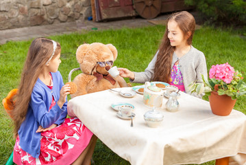 girls having tea party with teddy bear at yard