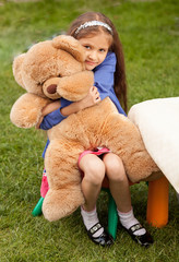 girl hugging big teddy bear while sitting on chair at yard