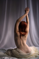 Back view of a sensual woman sitting naked in bed
