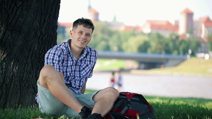 Portrait of young happy relaxed student in city park