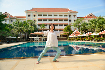 Healthy woman doing yoga exercises by pool in hotel