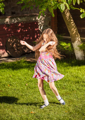 young girl dancing on grass at sunny day