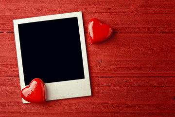 Blank photo and small red hearts on grunge background