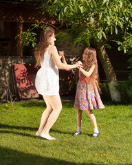 sisters having party and dancing on grass at yard