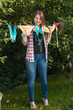 woman hanging swimsuits on clothesline at garden