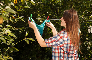 woman hanging blue bikini on clothesline at garden