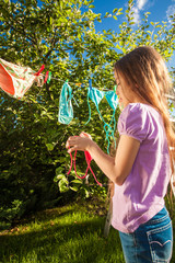 photo of young girl drying clothes on clothesline