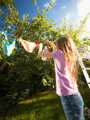girl doing laundry and drying clothes at garden