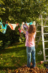 girl hanging clothes on clothesline at garden