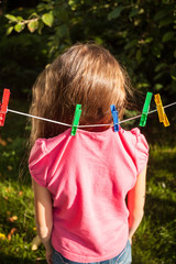 girl being hanged by shirt on clothesline