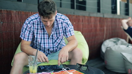 Young trendy man with tablet computer sitting in outdoor bar