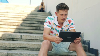 Young man with tablet computer sitting on stairs in city