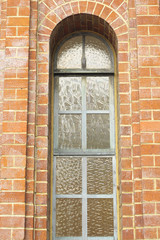 Ancient arched window with stained glass in brick wall