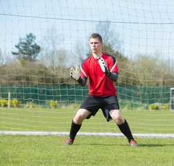 Goalkeeper in red ready to make a save