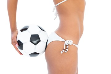 Fit girl in white bikini holding football