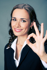 Happy business woman with okay gesture, over grey