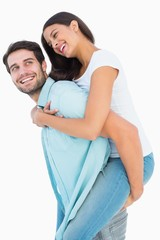 Happy casual man giving pretty girlfriend piggy back