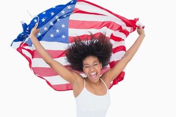 Pretty girl holding american flag cheering at camera