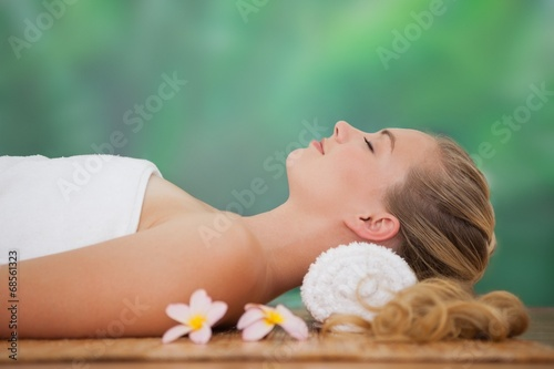 canvas print picture Peaceful blonde lying on bamboo mat with flowers