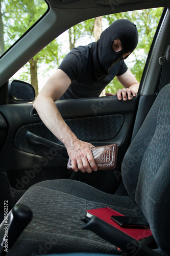 Burglar taking wallet from somebody's car