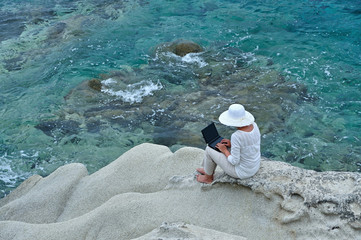 Woman wearing a hat sitting on the rock with laptop near the sea