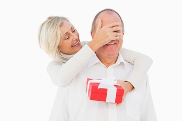 Older woman covering her partners eye while holding present