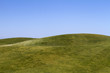 View of bare green hills with a blue sky. - 68562701
