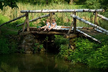 Twin Brothers Fishing from the Edge of  Wooden Bridge at Summer