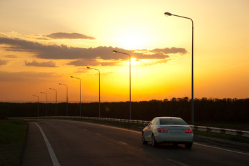 car driving on the highway at sunset