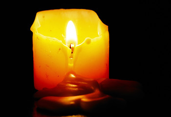 Close up view of half melted candle in the darkness.