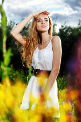 girl standing on flower glade and looks into the distance
