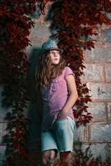 girl in a hat stands next to the with wild grapes