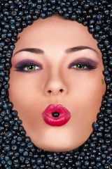 fashion woman in face with blueberry, berry in the mouth