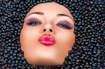Beautiful woman lying in blueberries and sends an air kiss