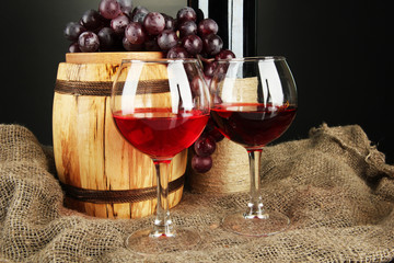 composition of wine and grapes on wooden barrel on sackcloth