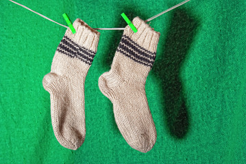A pair of white wool socks on a clothesline